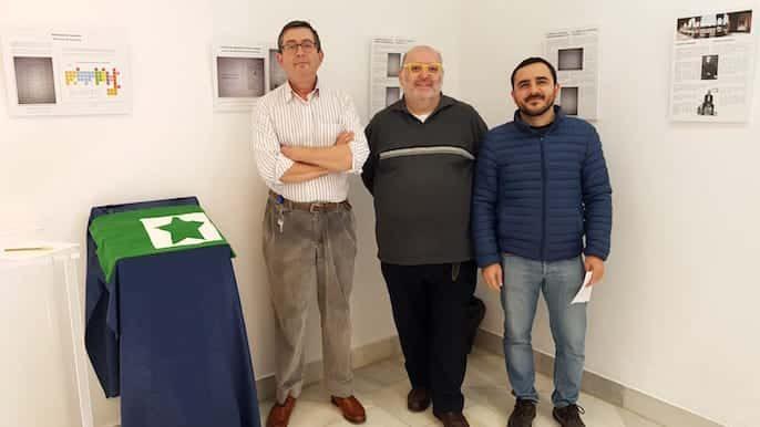 Tri esperantistoj kune pozantaj apud la ekspozicio