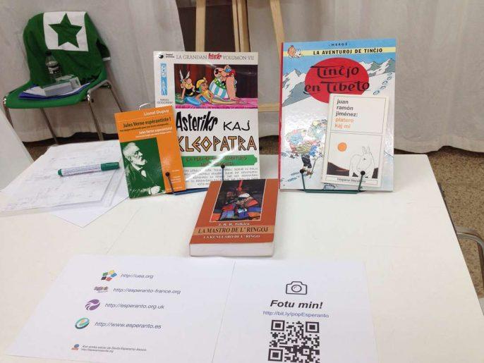 Una mesa con varios libros en esperanto y un cartel con un código QR.