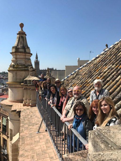 16 esperantistas y simpatizantes posando junto a la barandilla del tejado de la basílica. Al fondo puede verse la Giralda.